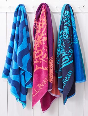 Three colorful towels hanging on towel hooks.