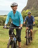 Two people mountain biking on an island trail.
