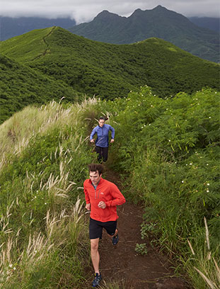 Two people running on a mountain trail.