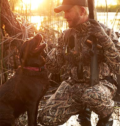 Man in camo crouched in reeds with dog and gun
