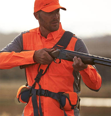 Man aiming gun wearing hunter orange upland clothing