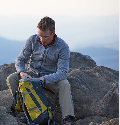 Man in activewear sitting on a mountaintop with his backpack.