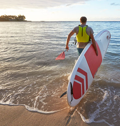 Man with stand up paddle board heading into the surf.