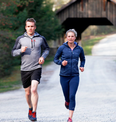 Man and woman in activewear running down a road.