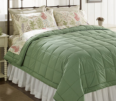 Cozy bed with green ultrasoft cotton comforter.
