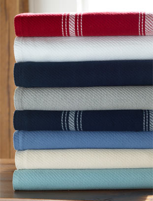 stack of plush blankets in a wide array of colors
