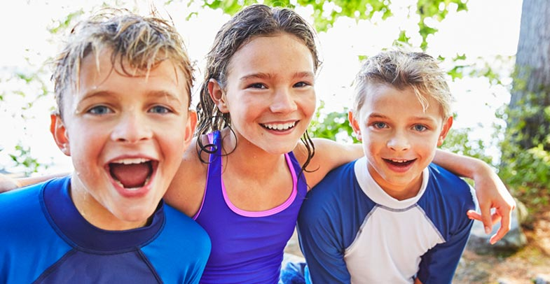 Image of smiling kids in swimwear.