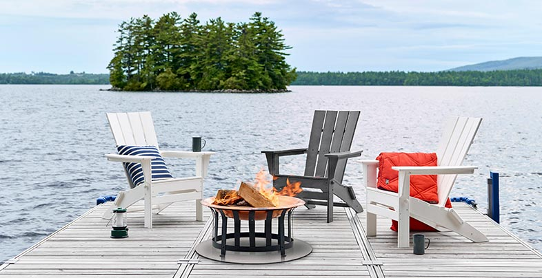 Adirondack chairs and fire pit lakeside.