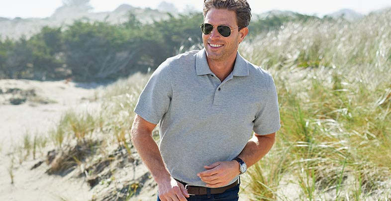 Man walking along beach in gray Double L Polo Shirt.