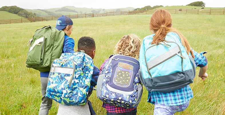 Kids walking to school through field with L.L.Bean Backpacks