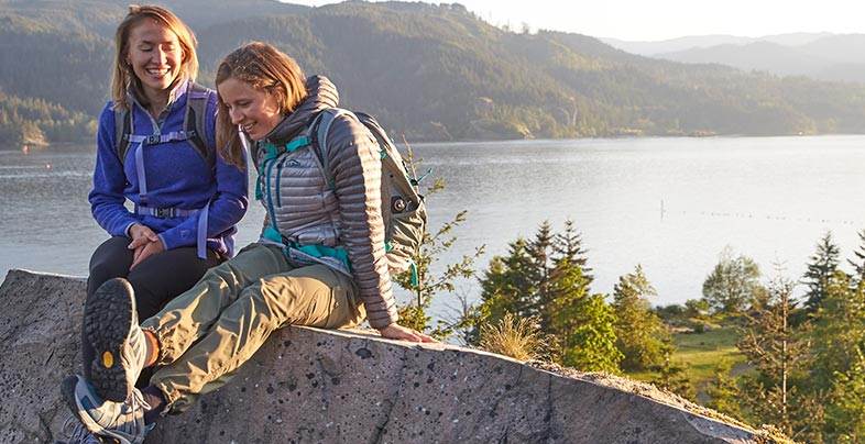 Two women in L.L.Bean hiking boots sitting in front of a lake.