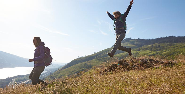 Hikers leaping through mountain fields.