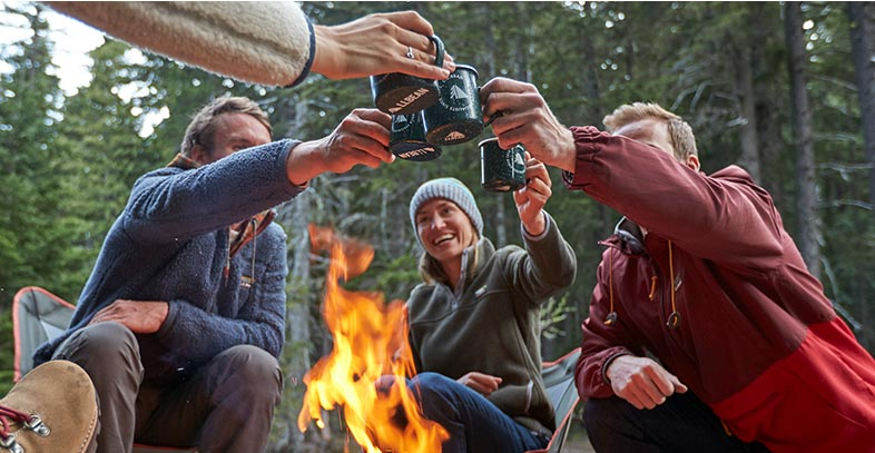 Group of people enjoying cups of coffee around a campfire.