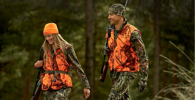 Man and woman in hunting gear.