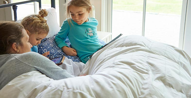 Mother and daughters reading in bed.