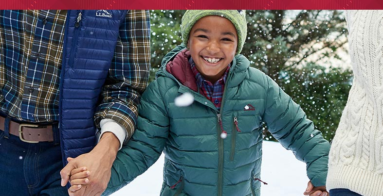 Little boy smiling with parents in Ultralight Down Jacket in snow
