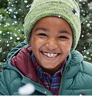 Smiling boy in snow storm.