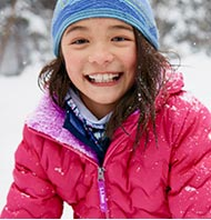 Girl in L.L.Bean down jacket smiling in the snow.