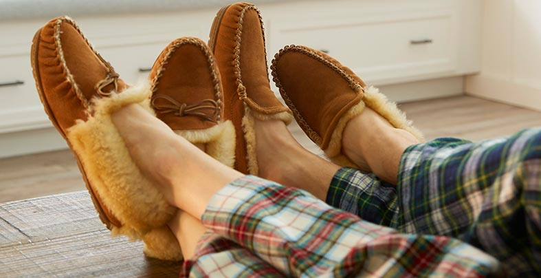 Two pairs of feet wearing L.L.Bean Wicked Good Slippers.