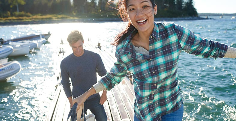 Woman in flannel shirt walking on dock by the water