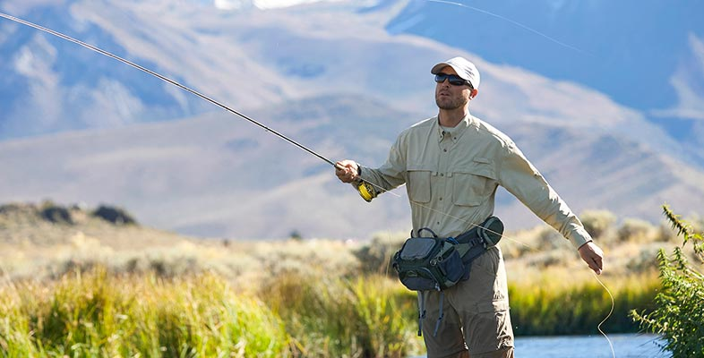 Man fly fishing in front of mountains.