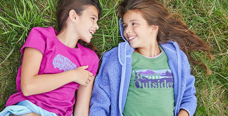 Girls lying in grass laughing