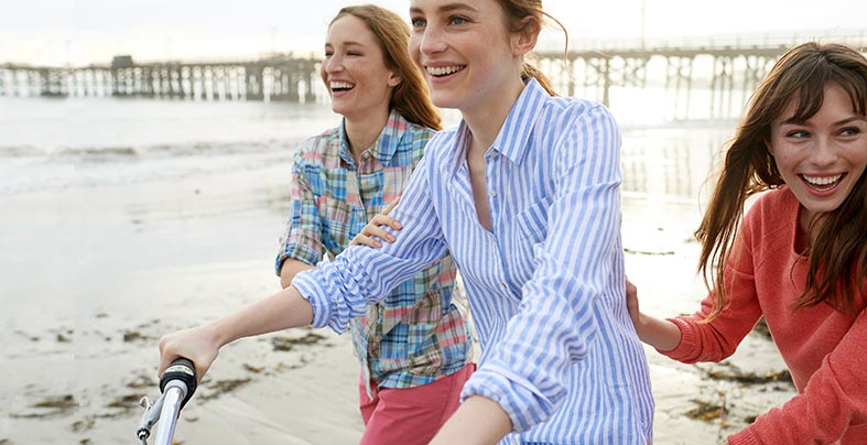 Women in linen shirts riding bikes along beach