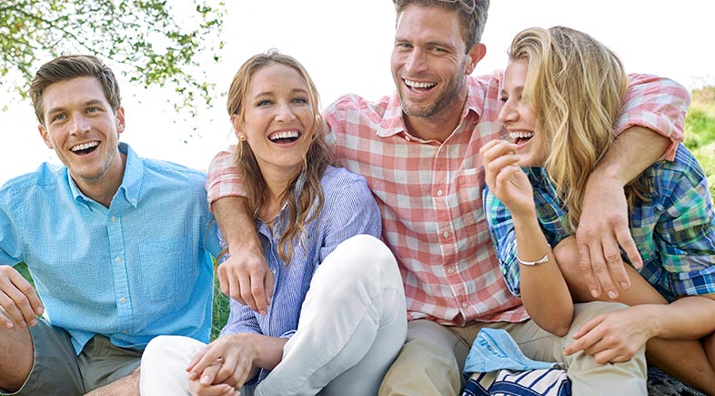 A laughing family wearing lightweight summer clothing.