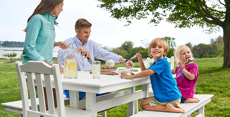 Family eating around outdoor table.