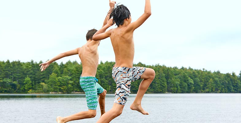 Boys jumping in the water wearing L.L. Bean suits.