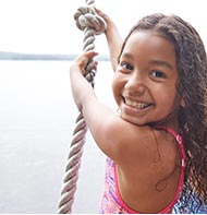 Smiling girl on a rope swing in an L.L.Bean swimsuit.