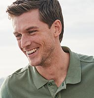 Laughing man in a polo shirt.