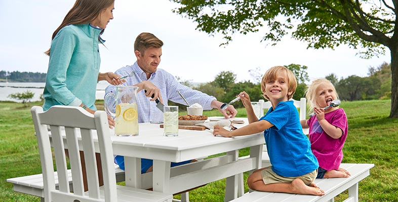 Family enjoying a meal outside on the L.L.Bean outdoor farmhouse table.