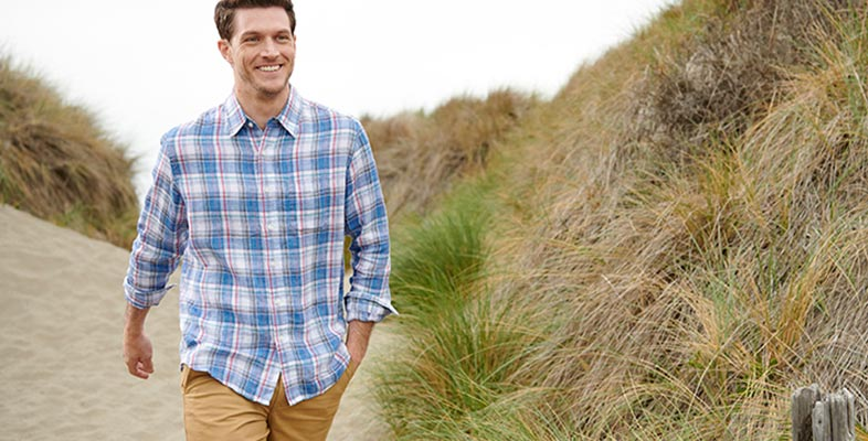 Man walking near a beach dune wearing an L.L.Bean linen shirt.