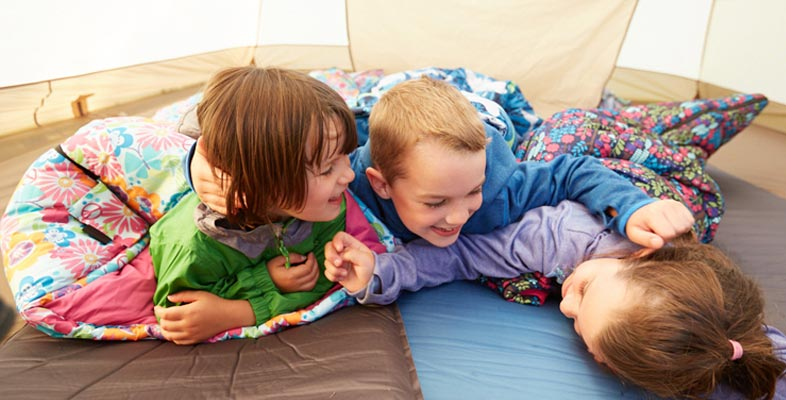 Kids playing in sleeping bags in a tent.