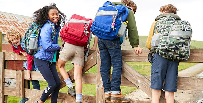 Kids playing on a fence with L.L. Bean backpacks.