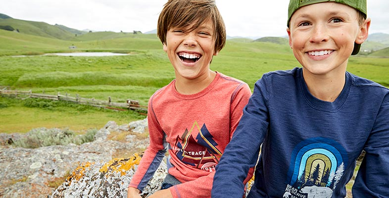 Two boys wearing L.L.Bean Tee Shirts sitting on rocks.