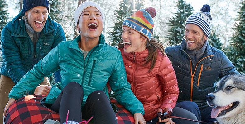 Friends sledding in L.L.Bean winter outerwear.