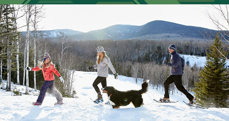Family enjoying a snowshoe adventure with their dog.