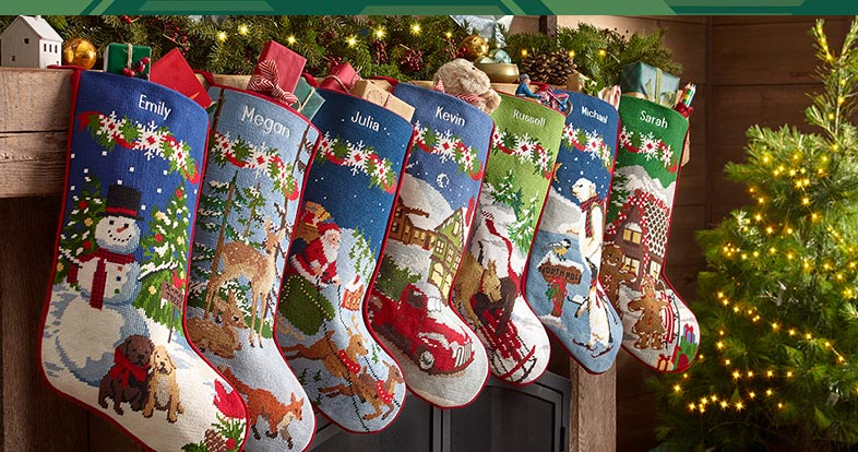 A beautiful selection of needlepoint stockings hung on a mantle.