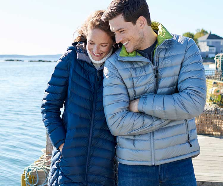 Man and woman on the beach in L.L.Bean Ultralight 850 Down Jackets.