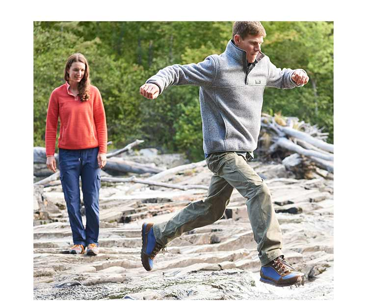 Man and woman hopping on rocks in trail pants.