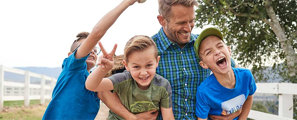 Man and children laughing together.