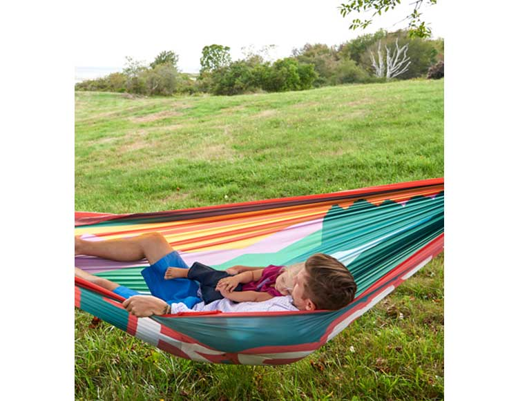 Man and child lounging in hammock.