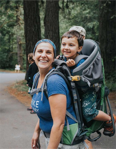 Mom smiling at camera with kid on her back about to start a hike