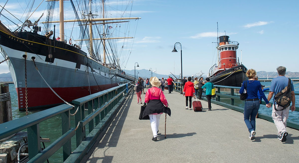 People walking along the pier at San Francisco Maritime National Historical Park.