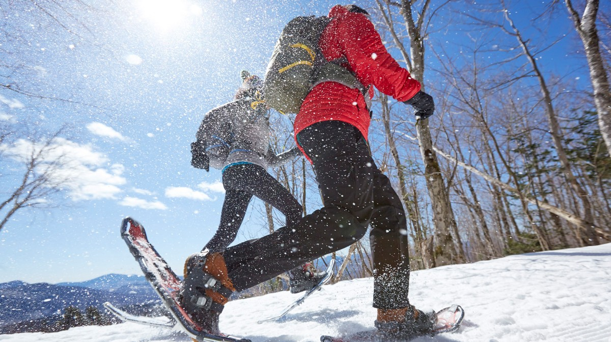 Photo of a couple snowshoeing on a mountain.