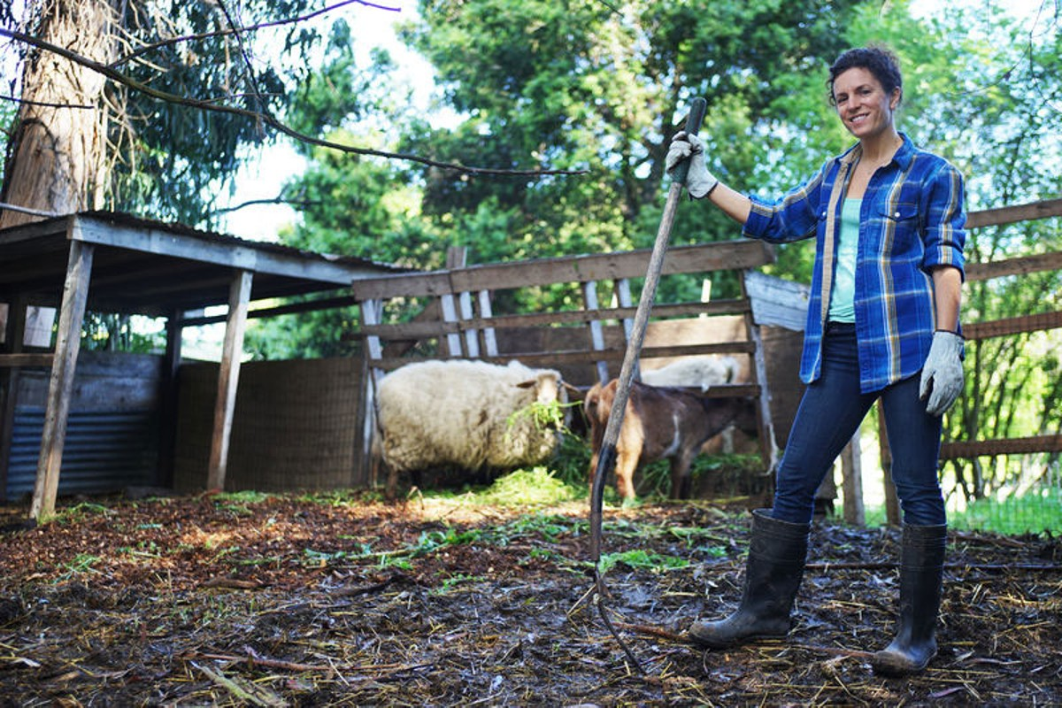 A woman taking care of her farm animals in her backyard.