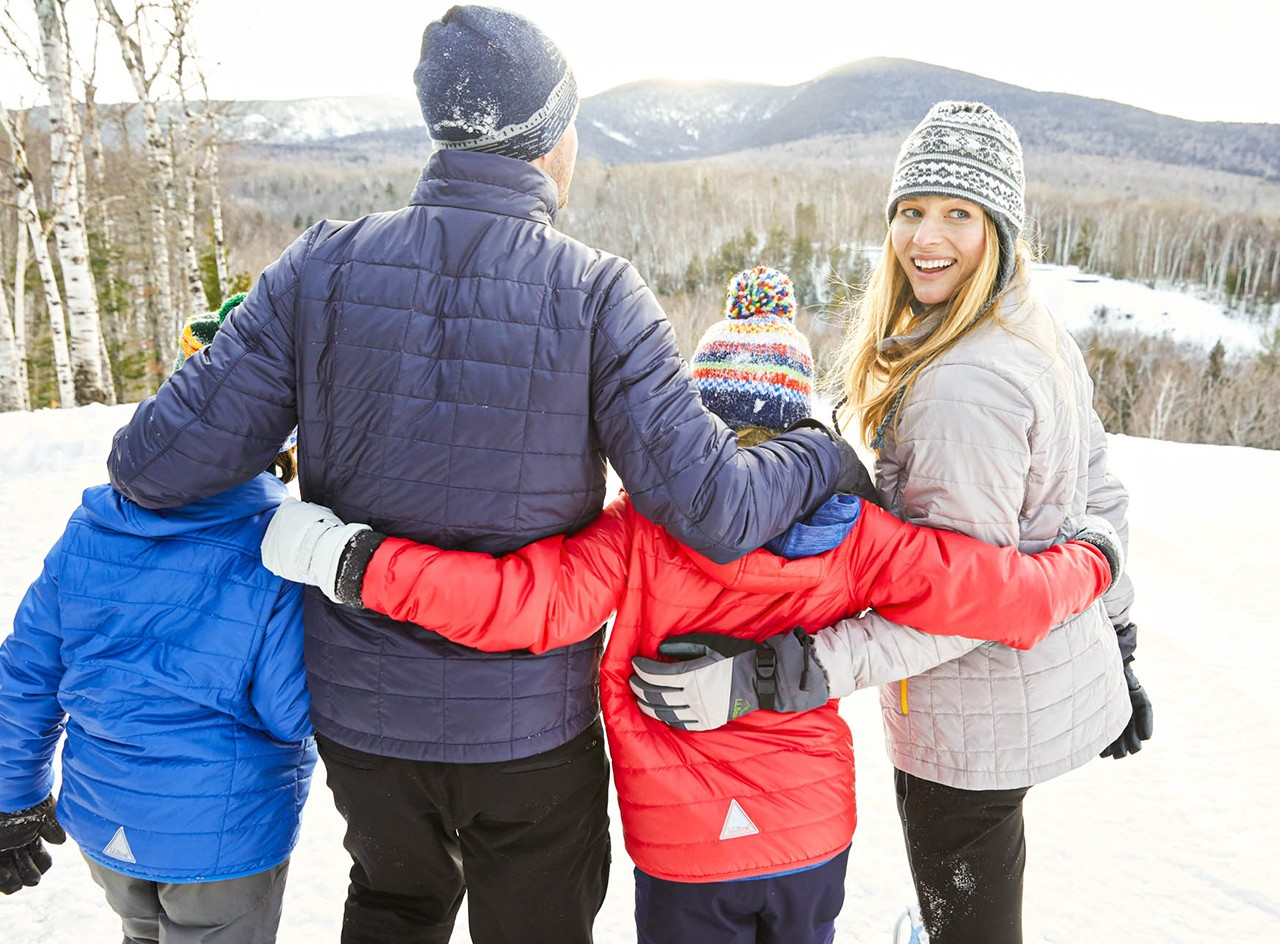 A family dressed in L.L. Bean winter jackets walking in the snow.