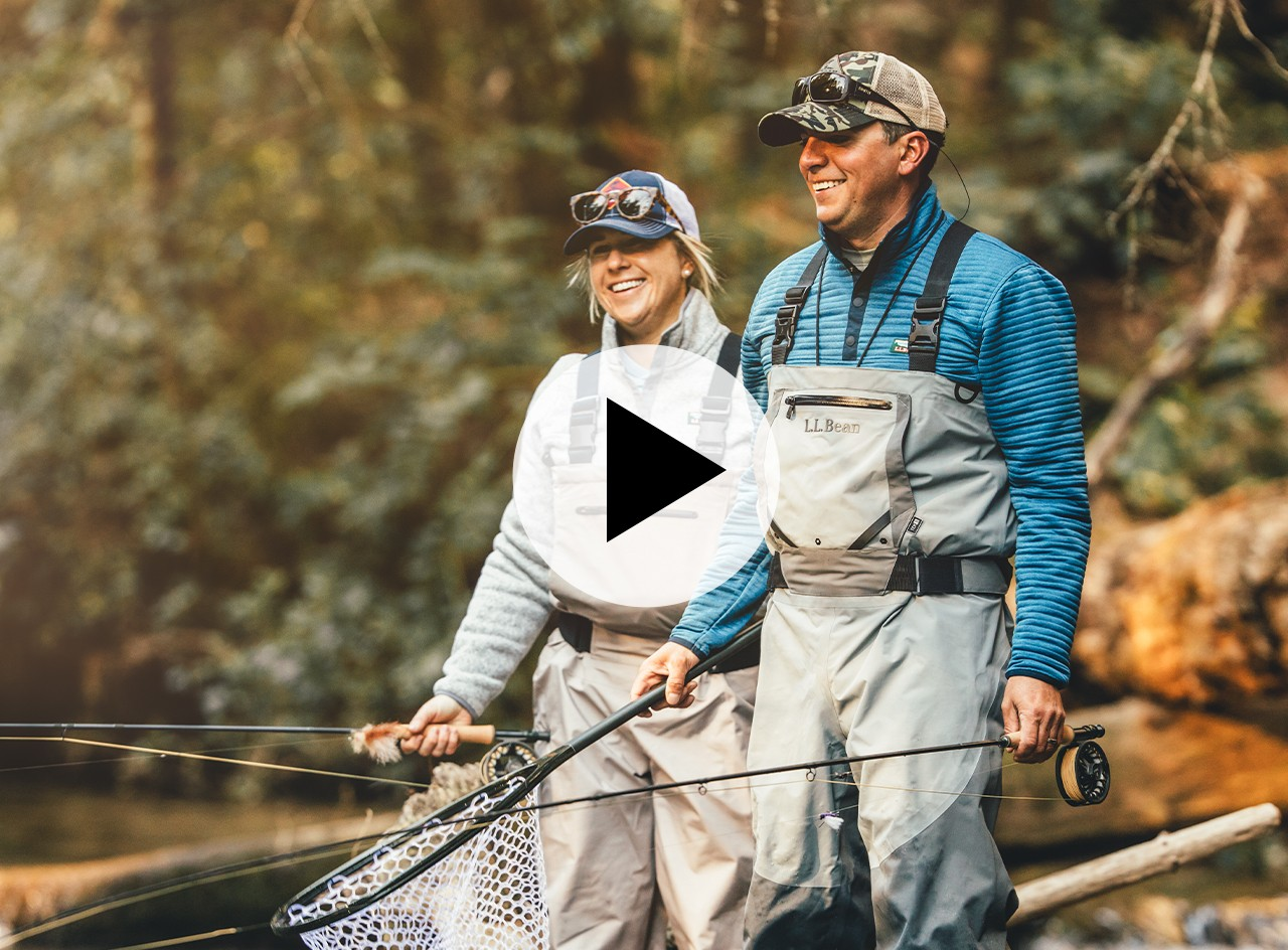 A smiling man and woman standing knee deep in water with fly fishing equipment.